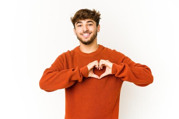 Jovem árabe em fundo branco, sorrindo e mostrando uma forma de coração com as mãos.