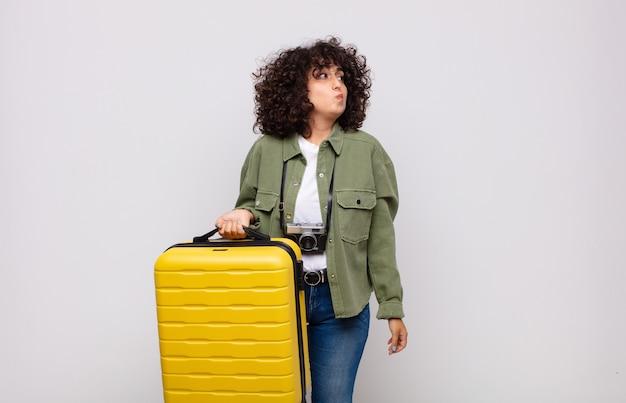 Jovem árabe encolhendo os ombros, sentindo-se confusa e incerta, duvidando com os braços cruzados e olhar perplexo conceito de viagens