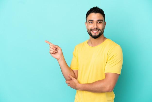 Jovem árabe isolado em um fundo azul apontando o dedo para o lado