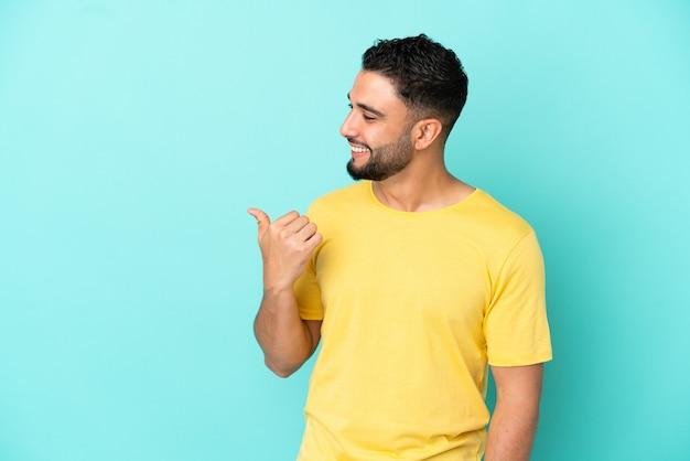 Jovem árabe isolado em um fundo azul apontando para o lado para apresentar um produto