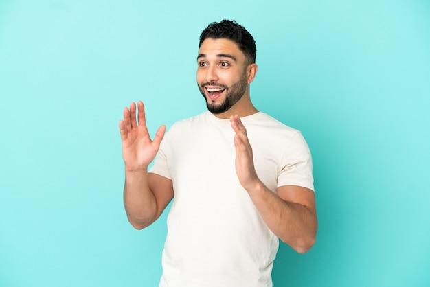 Jovem árabe isolado em um fundo azul com expressão facial surpresa