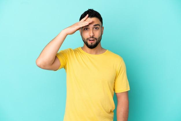 Jovem árabe isolado em um fundo azul percebeu algo e pretende a solução