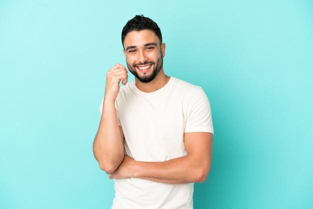 Jovem árabe isolado em um fundo azul rindo