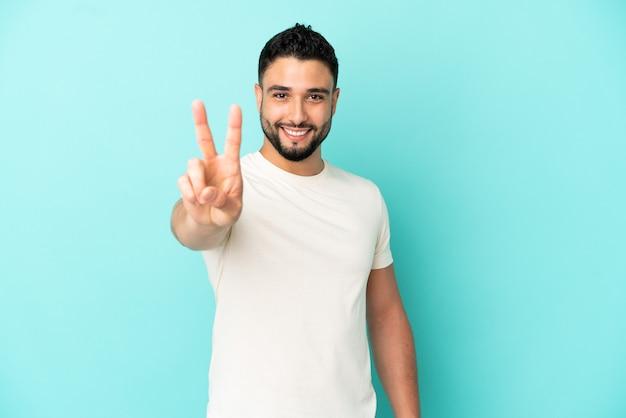 Jovem árabe isolado em um fundo azul sorrindo e mostrando sinal de vitória