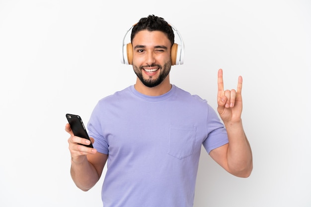 Jovem árabe isolado em um fundo branco ouvindo música com um celular fazendo gesto de rock