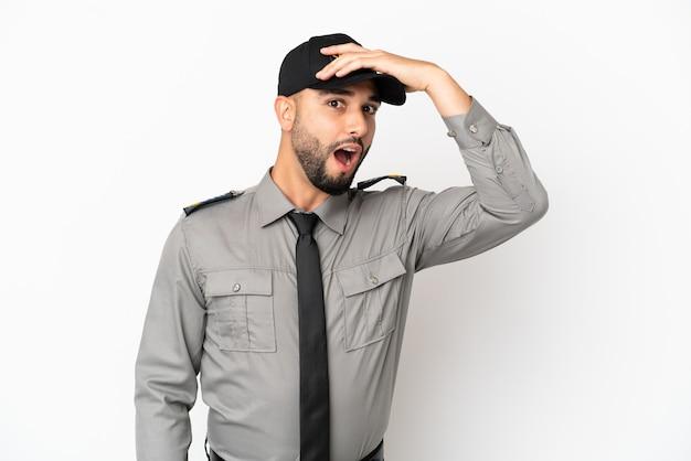 Jovem árabe isolado no fundo branco fazendo gesto de surpresa enquanto olha para o lado