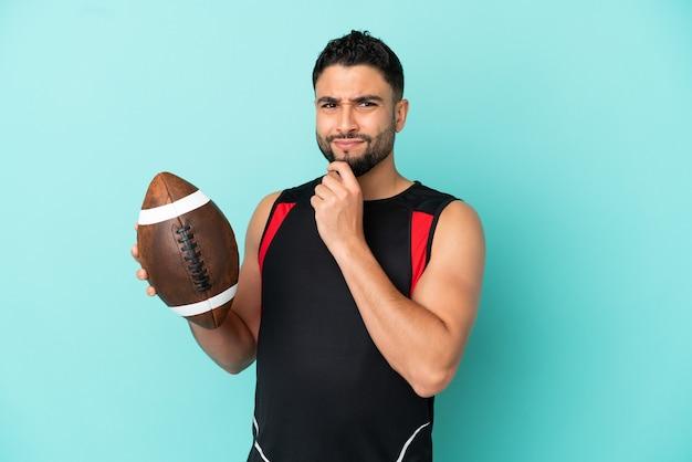 Jovem árabe jogando rugby isolado em um fundo azul, tendo dúvidas e pensando