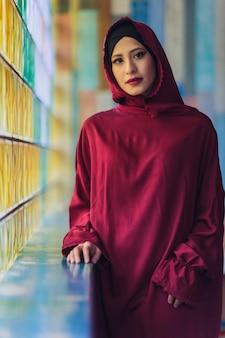 Jovem árabe muçulmana sentada em um café