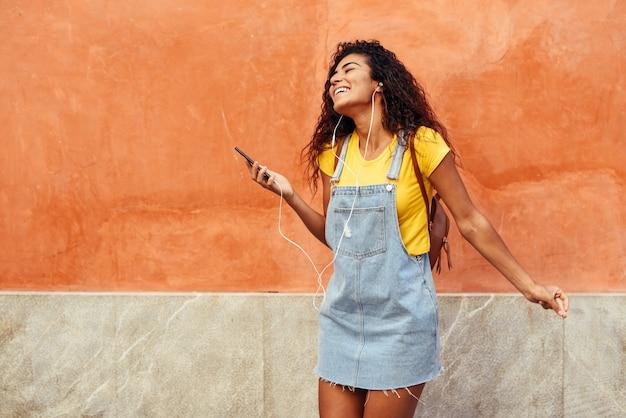 Jovem, árabe, mulher, escutar música, com, fones ouvido, ao ar livre