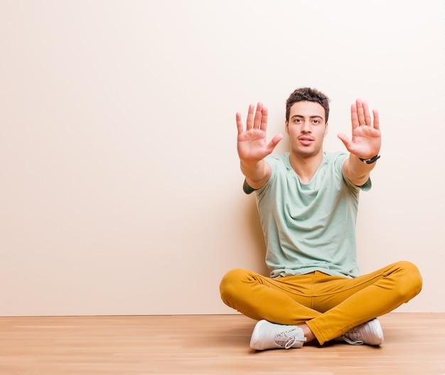 Jovem árabe olhando sério, infeliz, irritado e descontente proibindo a entrada ou dizendo pare com as duas palmas abertas, sentado no chão
