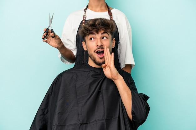 Jovem árabe pronto para cortar o cabelo isolado em um fundo azul está contando uma notícia secreta da frenagem e olhando para o lado