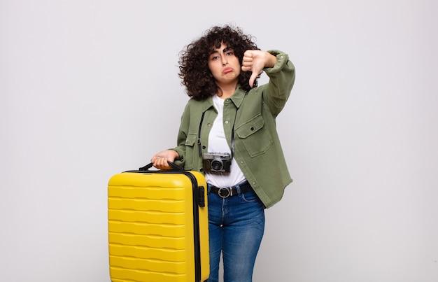 Jovem árabe se sentindo mal, irritada, irritada, decepcionada ou descontente, mostrando o polegar para baixo com um conceito de viagem de olhar sério