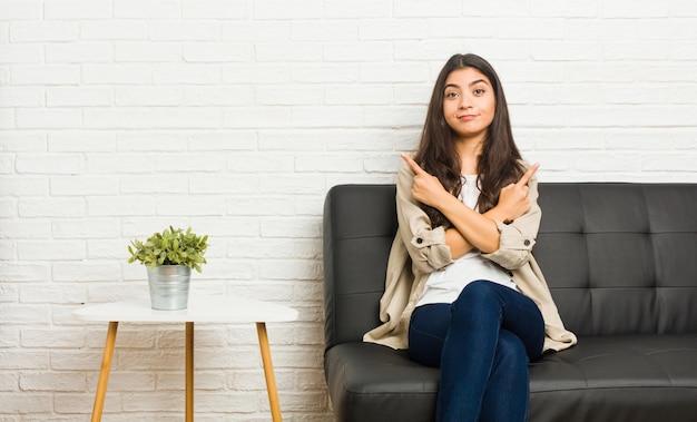 Jovem árabe sentado no sofá aponta lateralmente, está tentando escolher entre duas opções.