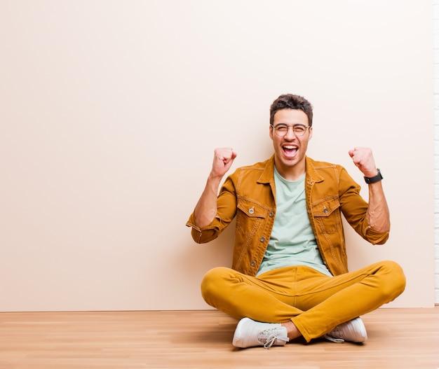 Jovem árabe, sentindo-se feliz, positivo e bem sucedido, comemorando a vitória, realizações ou boa sorte, sentado no chão