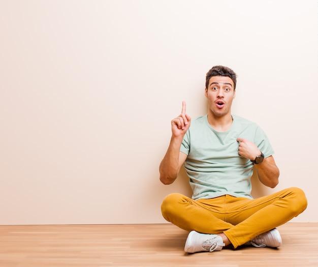 Jovem árabe, sentindo-se orgulhoso e surpreso, apontando para si mesmo com confiança, sentindo-se como o número um bem-sucedido sentado no chão