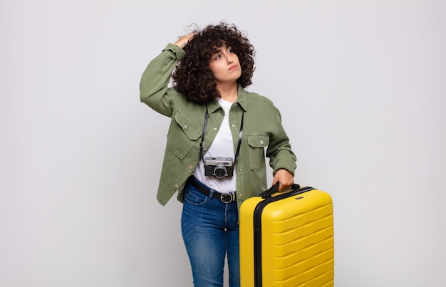 Jovem árabe sentindo-se perplexa e confusa, coçando a cabeça e olhando para o lado conceito de viagem