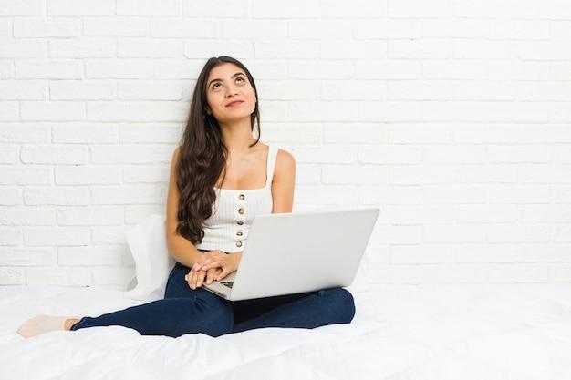 Jovem árabe trabalhando com seu laptop na cama, sonhando em alcançar objetivos e propósitos
