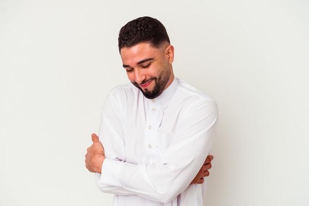 Jovem árabe vestindo roupas típicas árabes, isoladas em abraços brancos, sorrindo despreocupado e feliz.