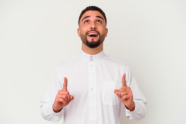 Jovem árabe vestindo roupas típicas árabes, isoladas na parede branca, apontando para cima com a boca aberta.