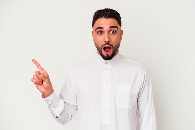 Jovem árabe vestindo roupas típicas árabes isoladas na parede branca apontando para o lado