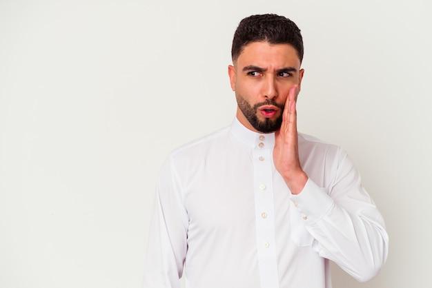 Jovem árabe vestindo roupas típicas árabes, isoladas na parede branca, contando uma notícia secreta da travagem e olhando para o lado