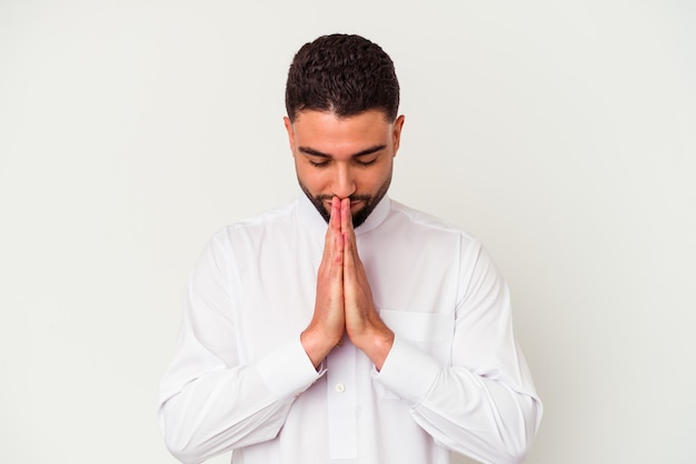 Jovem árabe vestindo roupas típicas árabes, isoladas na parede branca, de mãos dadas para orar perto da boca, sente-se confiante.