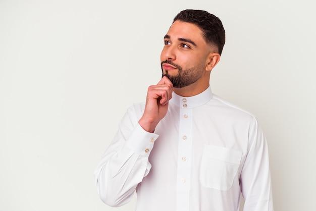Jovem árabe vestindo roupas típicas árabes, isoladas na parede branca, olhando de soslaio com expressão duvidosa e cética.