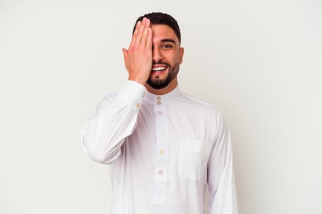 Jovem árabe vestindo roupas típicas árabes, isoladas na parede branca, se divertindo cobrindo metade do rosto com a palma da mão.