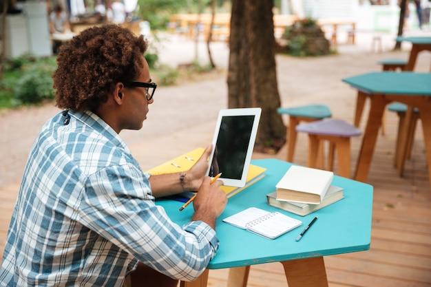 Jovem arficano cacheado usando tablet de tela em branco em uma cafeteria ao ar livre