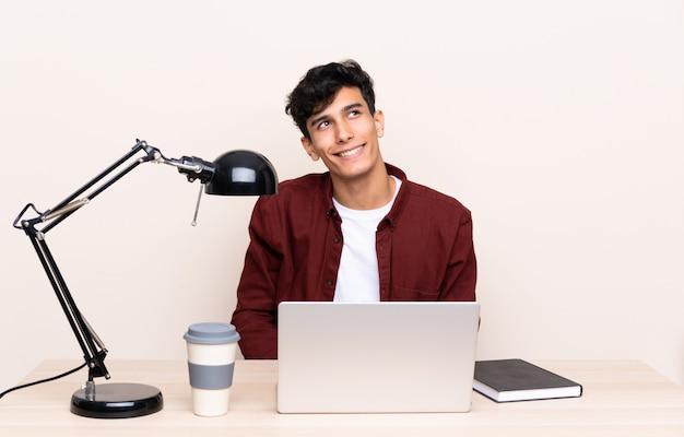 Jovem argentino em uma mesa com um laptop em seu local de trabalho rindo e olhando para cima