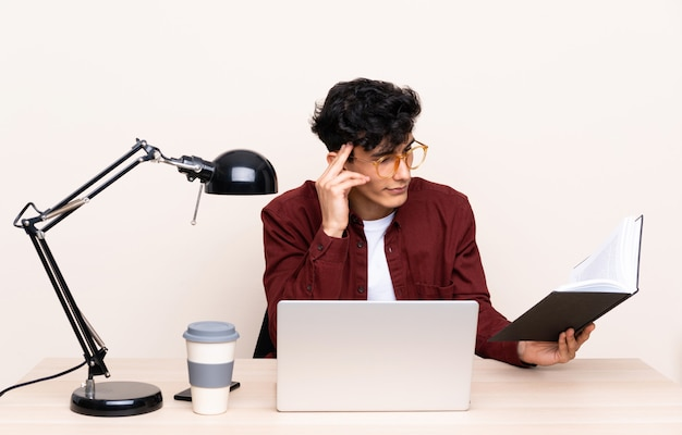 Jovem argentino em uma mesa com um laptop em seu local de trabalho