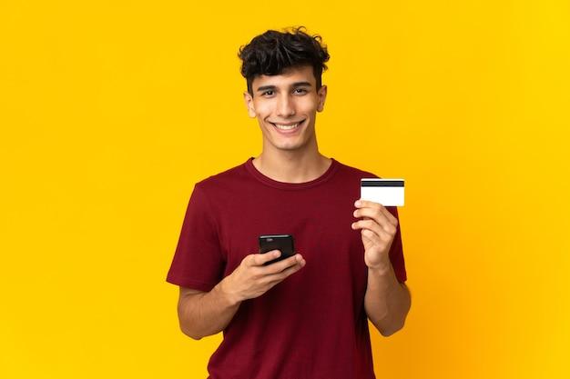 Jovem argentino isolado em um fundo amarelo comprando com o celular com um cartão de crédito