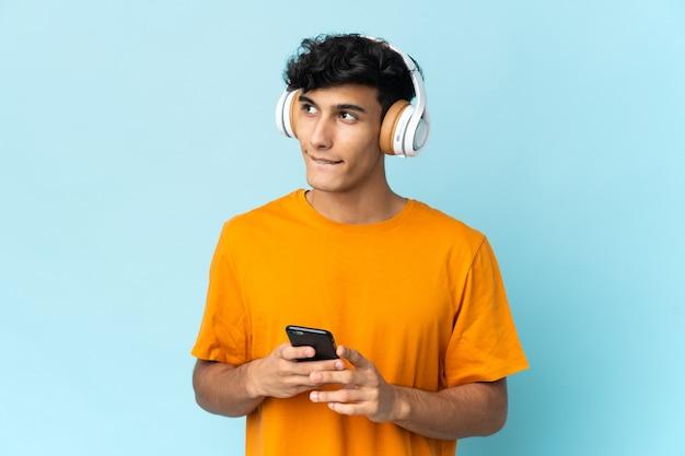 Jovem argentino isolado na parede ouvindo música com um celular e pensando