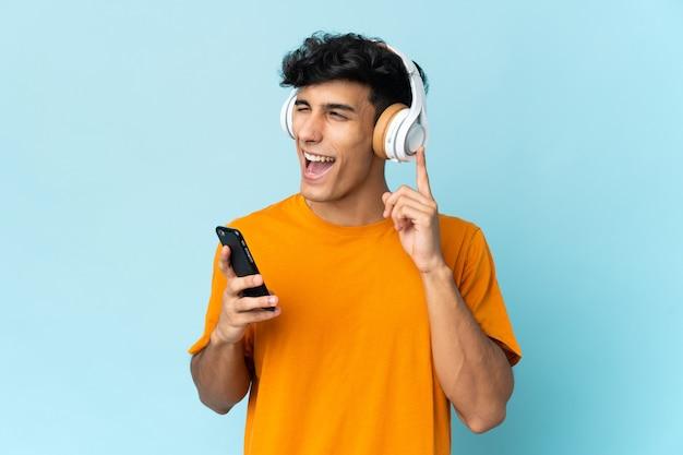 Jovem argentino isolado no fundo, ouvindo música com um celular e cantando