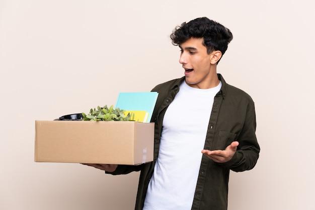 Jovem argentino, movendo-se em nova casa sobre parede isolada com expressão facial de surpresa