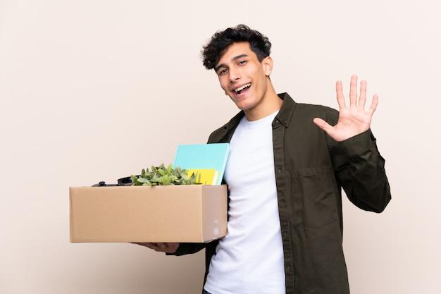 Jovem argentino, movendo-se em nova casa sobre parede isolada, saudando com mão com expressão feliz