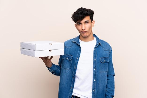 Jovem argentino segurando pizzas sobre parede isolada com expressão triste