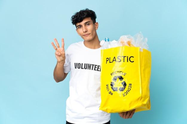 Jovem argentino segurando uma sacola cheia de plástico feliz e contando três com os dedos