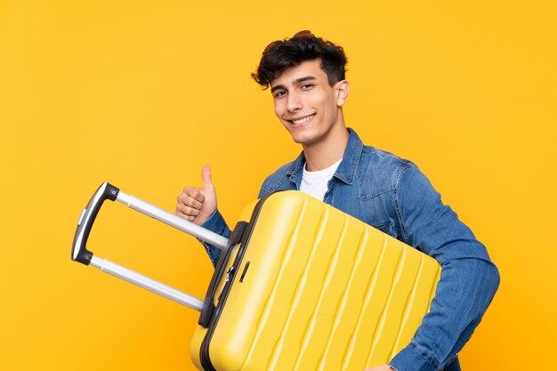 Jovem argentino sobre parede amarela isolada em férias com mala de viagem e com o polegar para cima