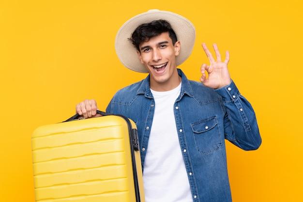 Jovem argentino sobre parede amarela isolada em férias com mala de viagem e um chapéu