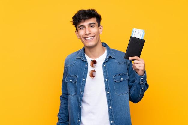 Jovem argentino sobre parede amarela isolada feliz em férias com bilhetes de avião e passaporte
