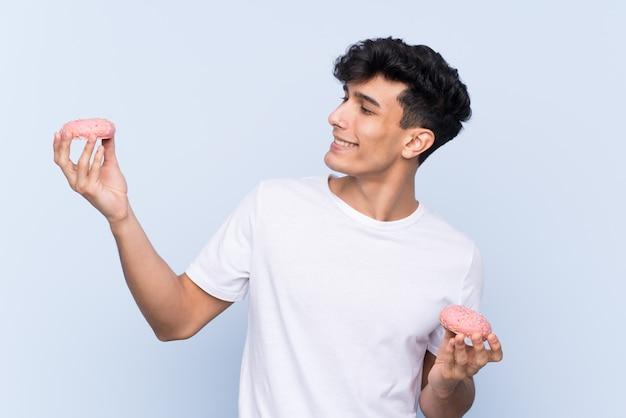 Jovem argentino sobre parede azul isolada segurando rosquinhas com expressão feliz