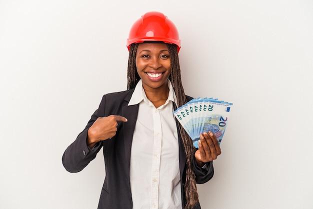 Jovem arquiteta afro-americana segurando contas isoladas em um fundo branco pessoa apontando com a mão para um espaço de cópia de camisa, orgulhosa e confiante