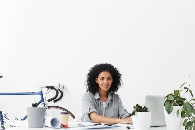 Jovem arquiteta autônoma de pele escura, cansada, mas feliz sentada em frente a um laptop aberto