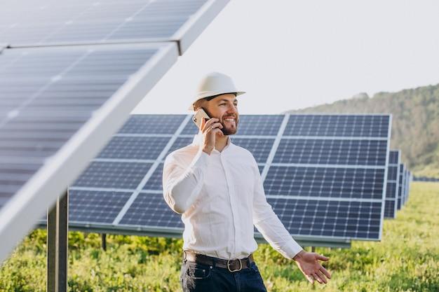 Jovem arquiteto ao lado de painéis solares falando ao telefone