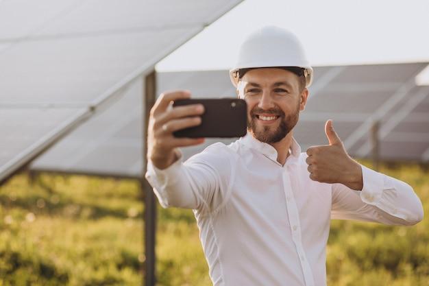 Jovem arquiteto ao lado de painéis solares
