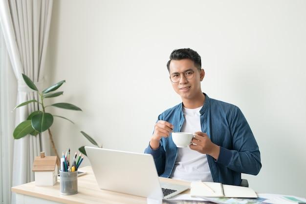 Jovem arquiteto asiático trabalhando, sorrindo para a câmera