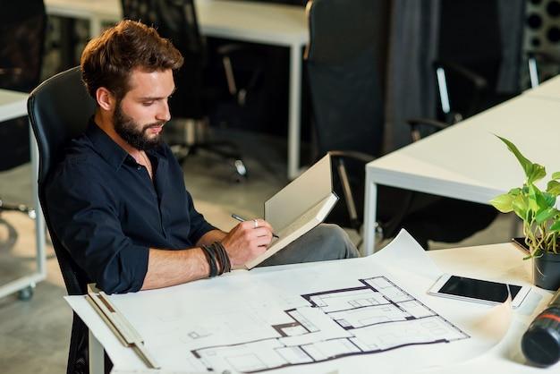 Jovem arquiteto barbudo trabalhando com arranhões em seu novo projeto Foto Premium