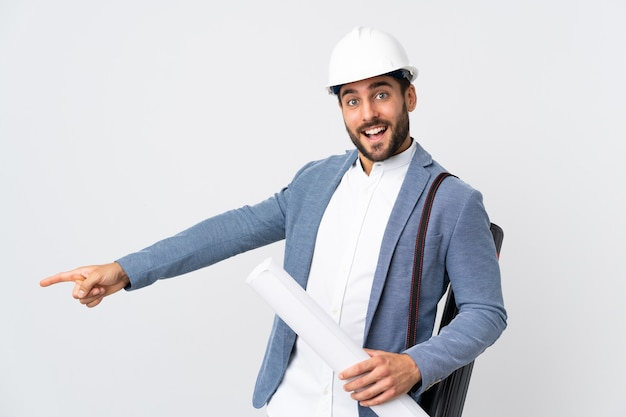 Jovem arquiteto com capacete e segurando plantas isoladas em branco apontando o dedo para o lado e apresentando um produto