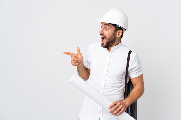 Jovem arquiteto com capacete e segurando plantas isoladas na parede branca apontando o dedo para o lado e apresentando um produto